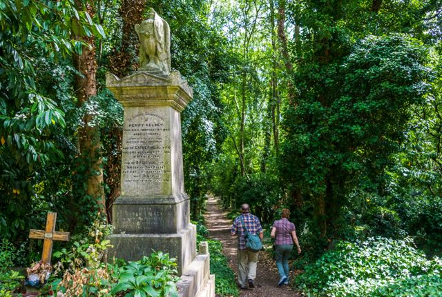 Roy and docent walk down path at Highgate Cemetery in London.