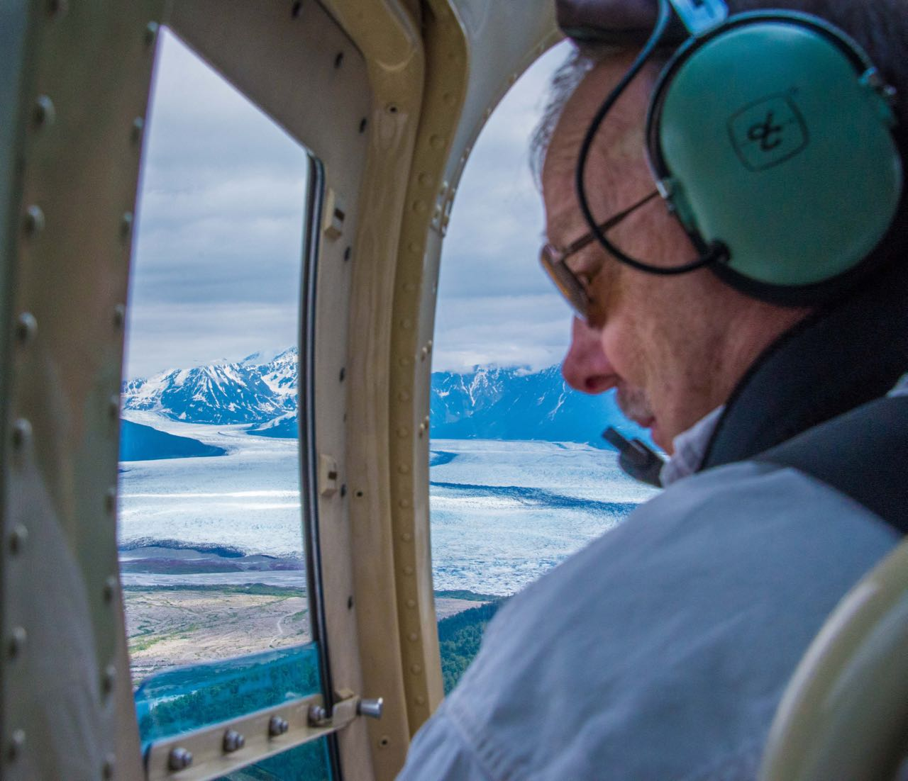 Looking out the window of helicopter flying over glaciers in Alaska