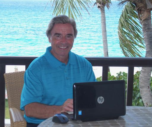 Tim Cotroneo sitting with his laptop in Anguilla.