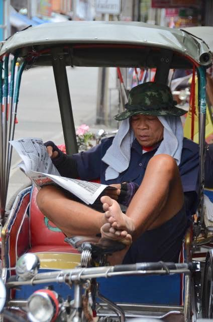 Tuk tuk driver reading news stories in Chiang Mai, Thailand