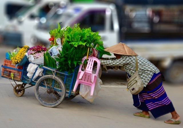 Woman pushing cart full of goods in Myanmar.  Your travel writing journey is sure to be easier than hers.