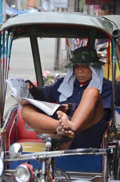 Tuk tuk driver reading news stories in Chiang Mai, Thailand